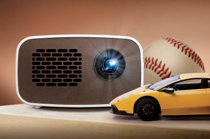 Front view of LG HD MiniBeam model PH300 beaming light on a table next to images of a baseball and supercar