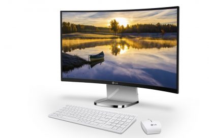 A right-side view of LG's curved All-In-One PC model 29V950 with a keyboard and mouse at its front