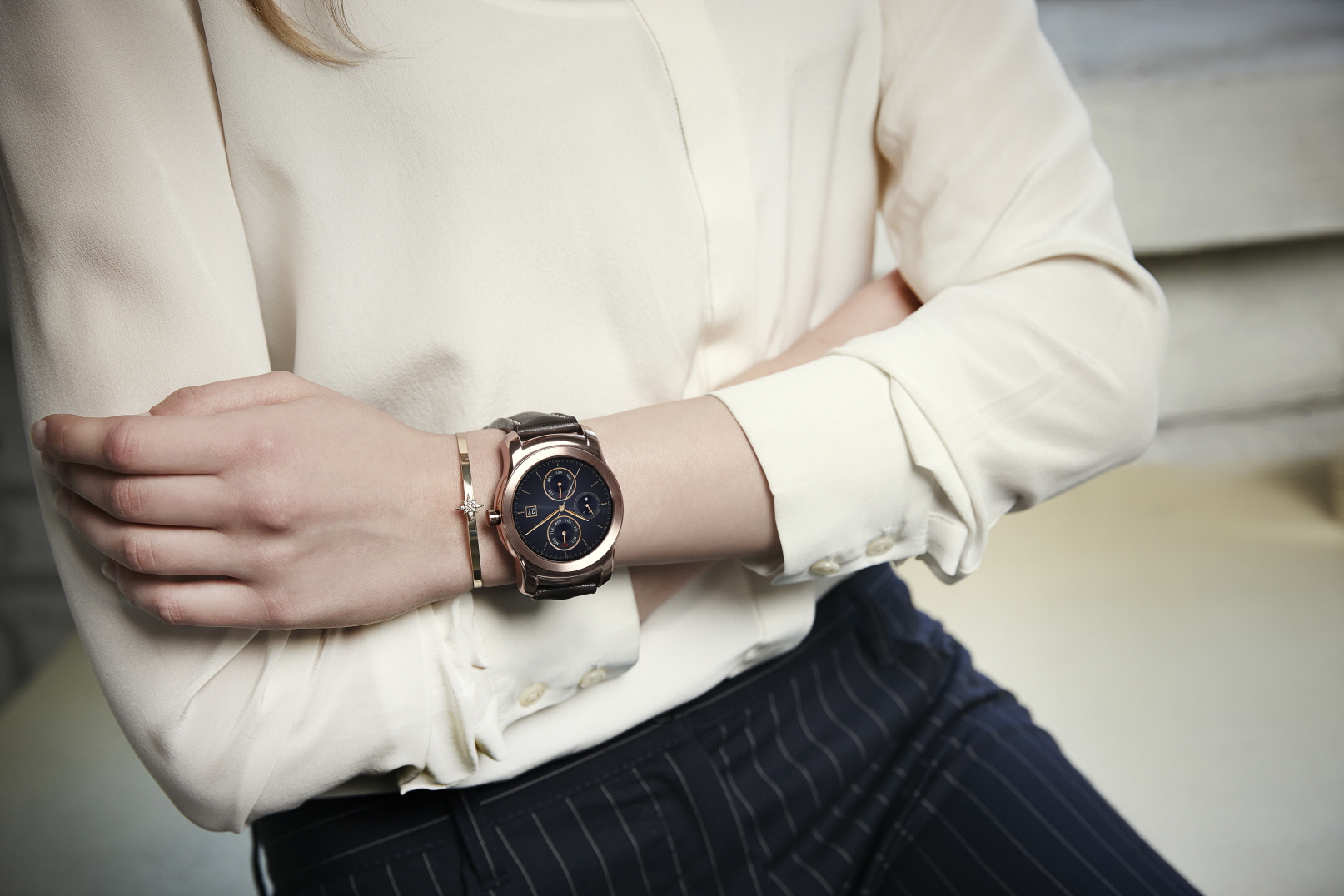 A woman folding her arms while wearing the LG Watch Urbane in gold.