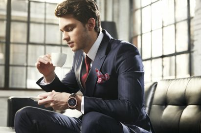 A man is holding up a cup of coffee wearing LG Watch Urbane in gold color.