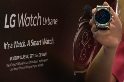 A woman holds the LG Watch Urbane in front of an large poster for the watch.