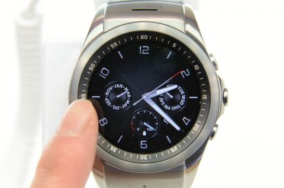 A finger approaching to a LG Watch Urbane.