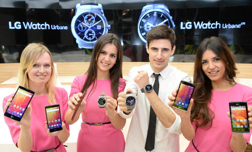 Four models are smiling at a camera holding LG smartphones and LG Watch Urbane at LG booth of MWC.