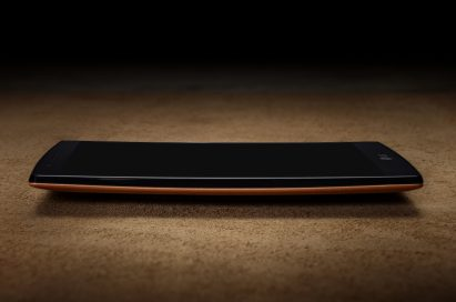 A side vie of the LG G4 wearing a brown leather when lying on a table.