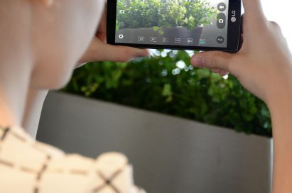 A woman taking a landscape picture with the LG G4 Beat.