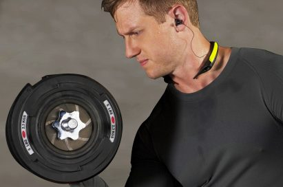 A man working out with a dumbbell while wearing the LG TONE Active.