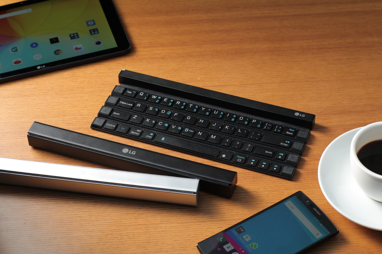 Three Rolly Keyboards displayed on the table with a G pad, an LG smartphone and a cup of coffee. Two of them are folded up with the other is ready to use.