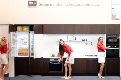 Three female models posing with LG Studio refrigerator, oven and Speed oven.