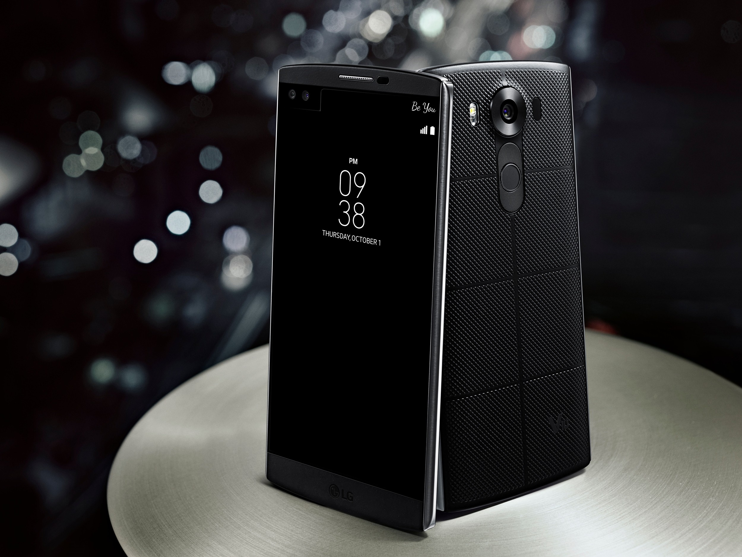 Two LG V10s in Space Black standing on a table, showing the front and back view of the device