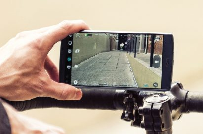 A person records a video on LG V10 propped on top of bicycle handles