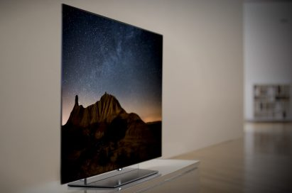 A left-side view of an LG OLED TV displaying a mountain scene at night