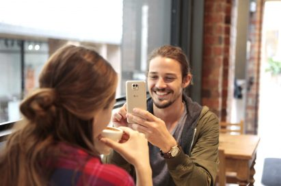 A woman is being photographed by a man with the LG X cam in White