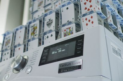 Closeup of LG Centum System™ washing machine and house of card built on it