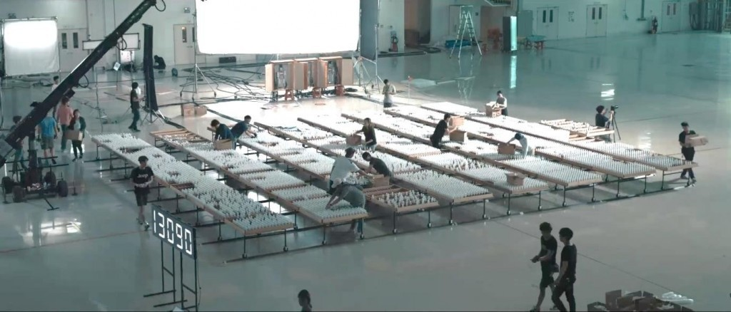 Several people working on constructing the bulb-based display in a large auditorium