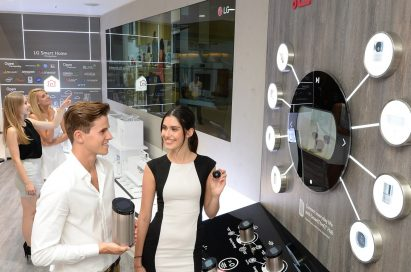Another view of male and female models holding SmartThinQ™ Hub and SmartThinQ™ Sensors in their hands at LG booth in IFA 2019