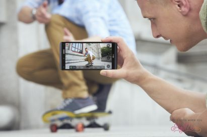 A man taking a video of a man skateboarding using the LG V20's Steady Record 2.0 feature