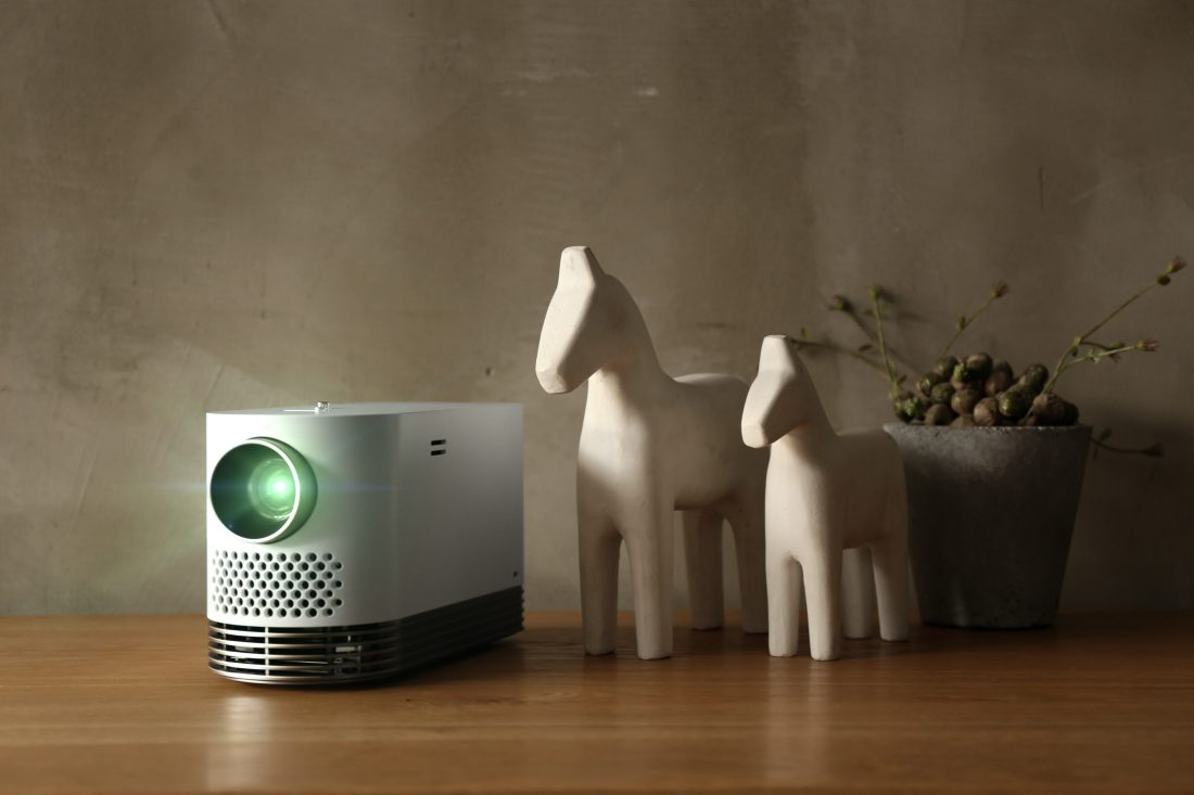 The LG Probeam Laser Projector (model HF80J) put on a table next to some decorative horses and a plant