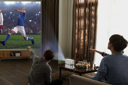 Three people watch a soccer game projected on the wall by the LG Probeam Laser Projector (model HF80J)