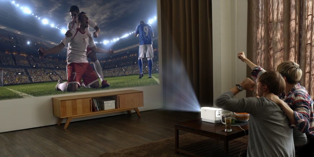 Two men watch a soccer game projected on the wall by the LG Probeam Laser Projector (model HF80J)