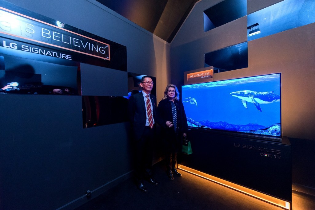 Visitors standing before a display at the LG SIGNATURE Gallery launch event in Paris