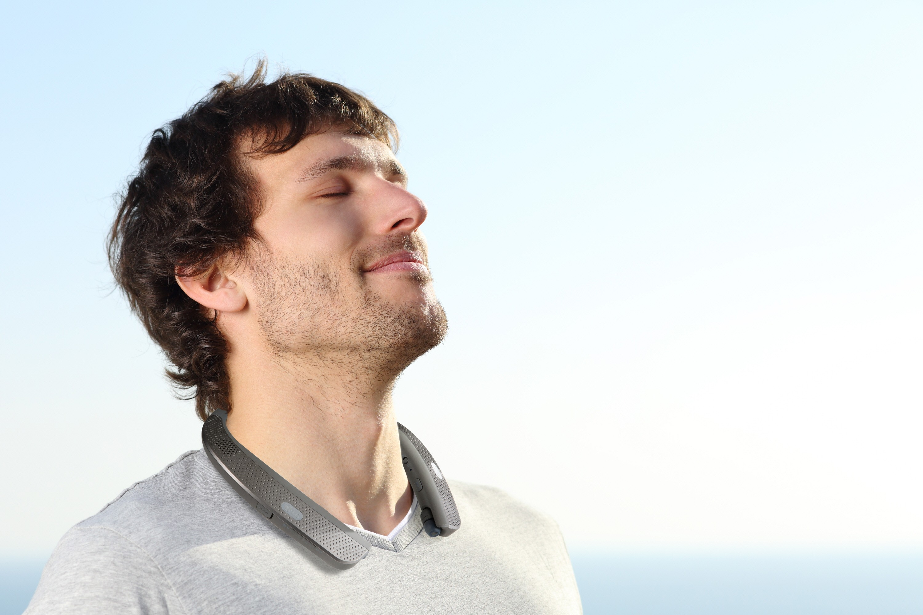 A man looking toward the sky with the LG Tone Studio around his neck