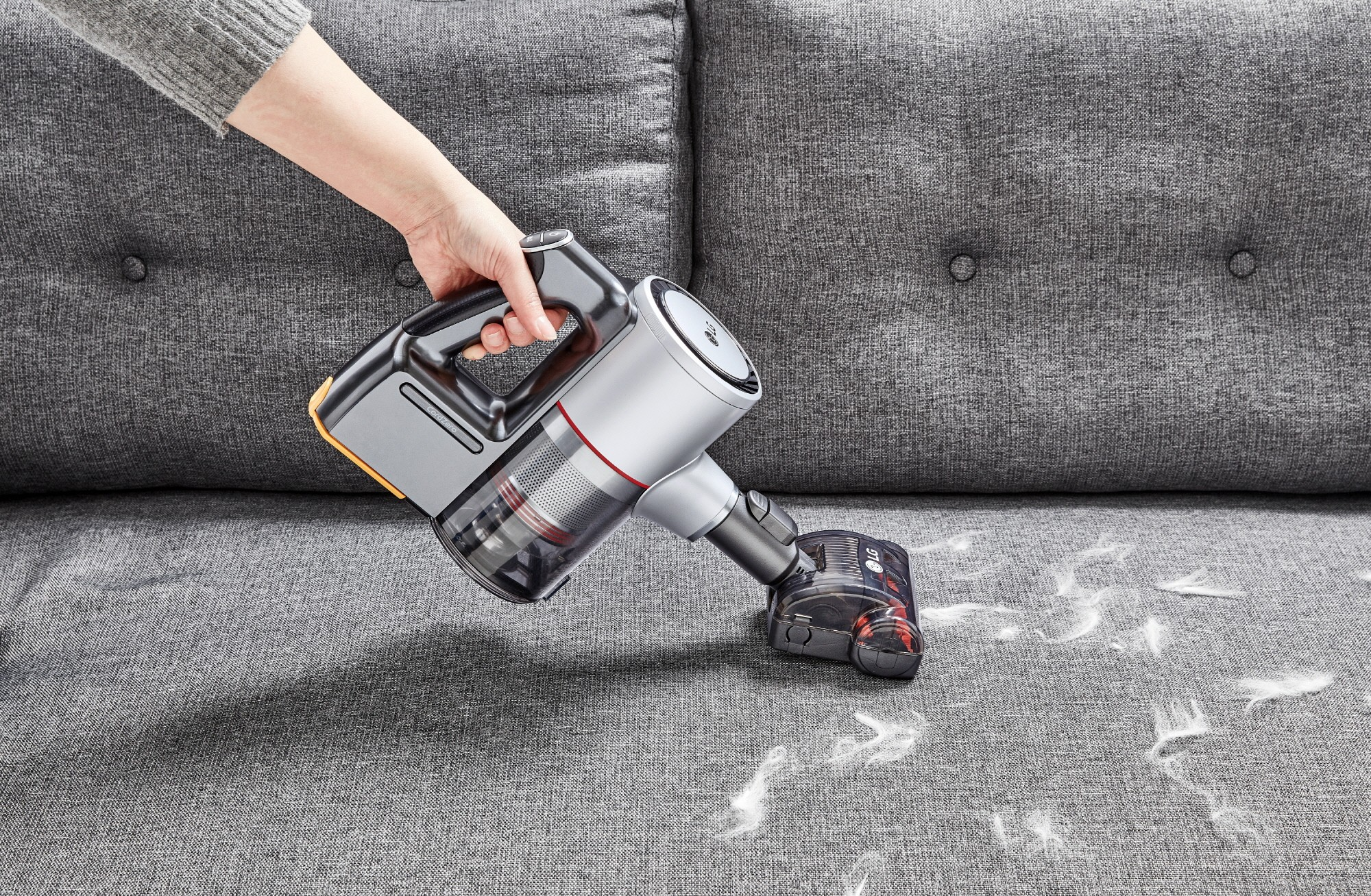 View of a person vacuuming up feathers from a couch with the LG CordZero Handstick