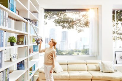 A woman vacuums bookshelves with the LG CordZero Handstick