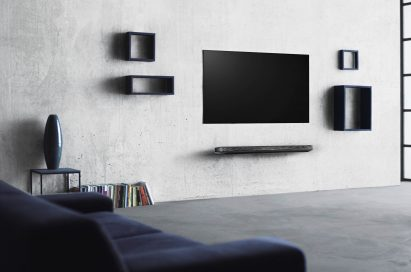 An LG SIGNATURE OLED TV W (model W7) is on the wall of an apartment, it is turned off but blends seamlessly with the art and décor.