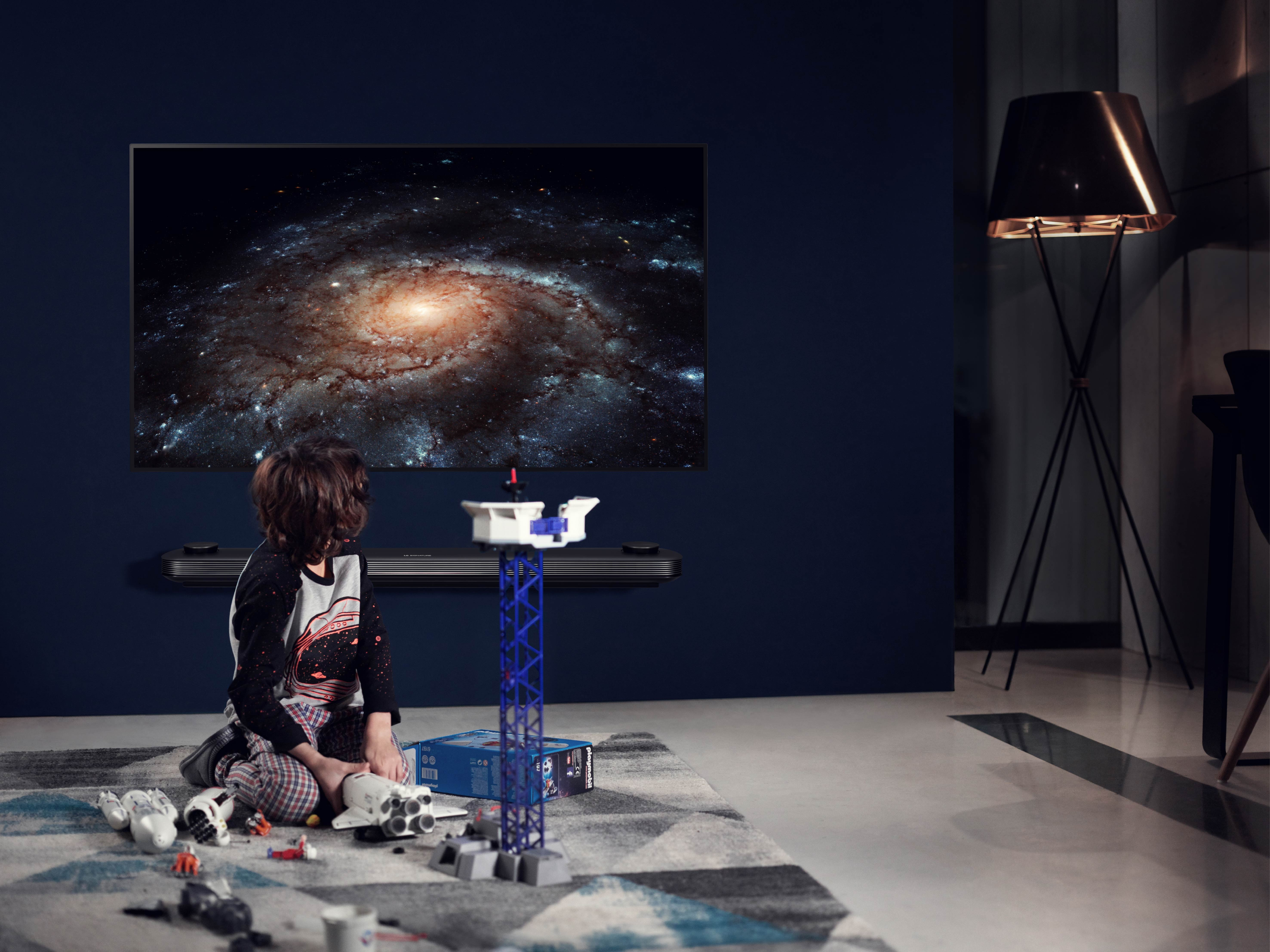 A small boy plays with space toys while the LG SIGNATURE OLED TV W is displayed on the wall with a picture of a galaxy on the screen.