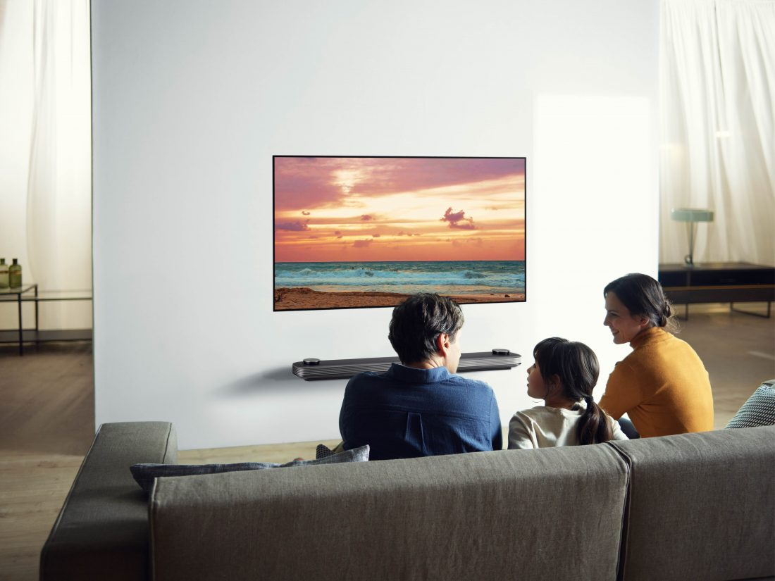 Another view of a family sitting in their living room looking at the LG SIGNATURE OLED TV W (model 7) which is mounted seamlessly on the wall