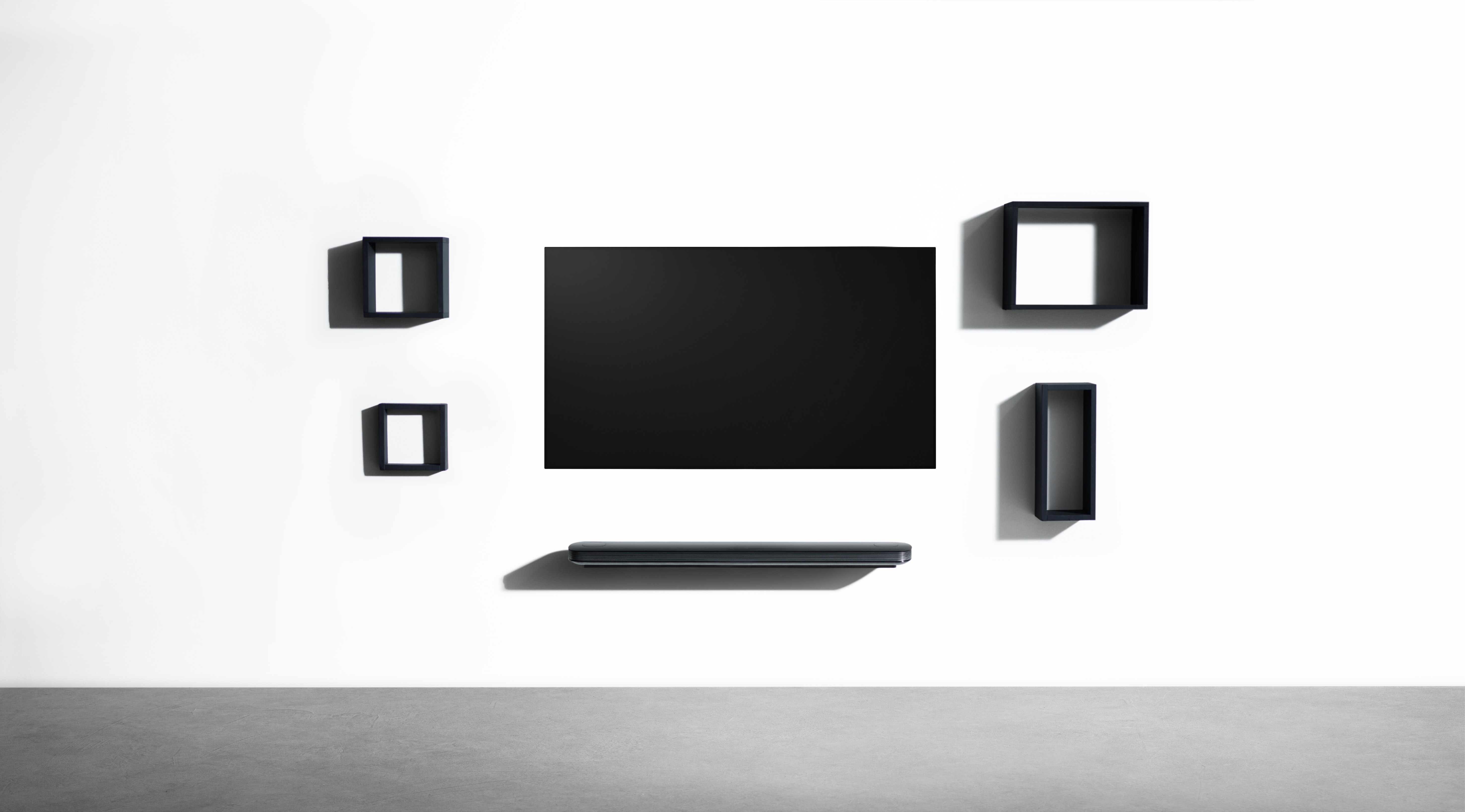 An LG SIGNATURE OLED TV W with a darkened screen hangs against the wall with black frames mounted decoratively around it