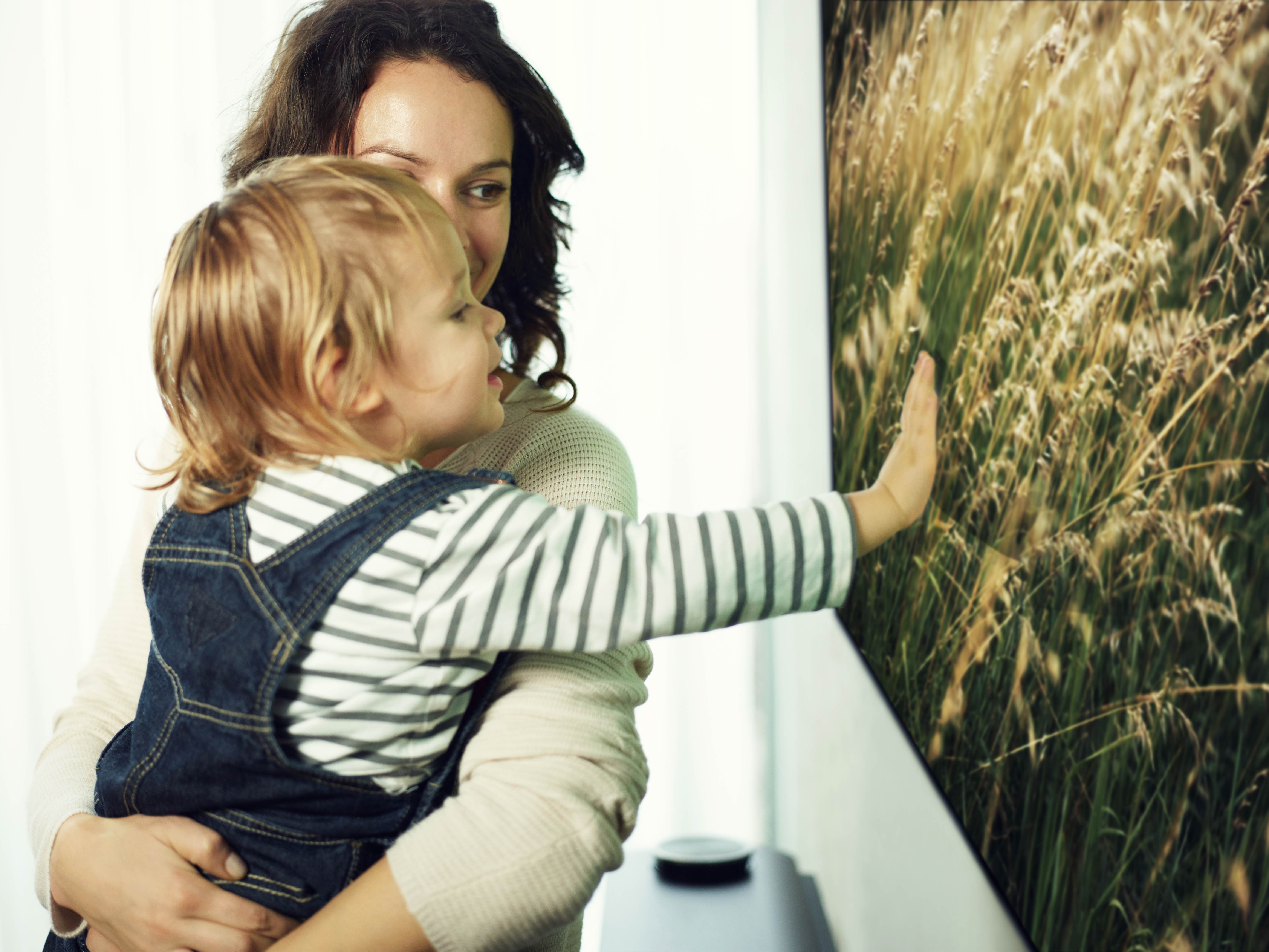 A mother and small child look at an LG SIGNATURE OLED TV W while the child is touching the screen.