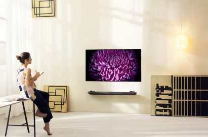 A woman sits on a desk while drawing a flower displayed on the LG SIGNATURE OLED TV W