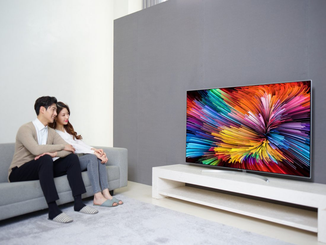A couple sits on a couch watching the LG SUPER UHD TV (model SJ95).
