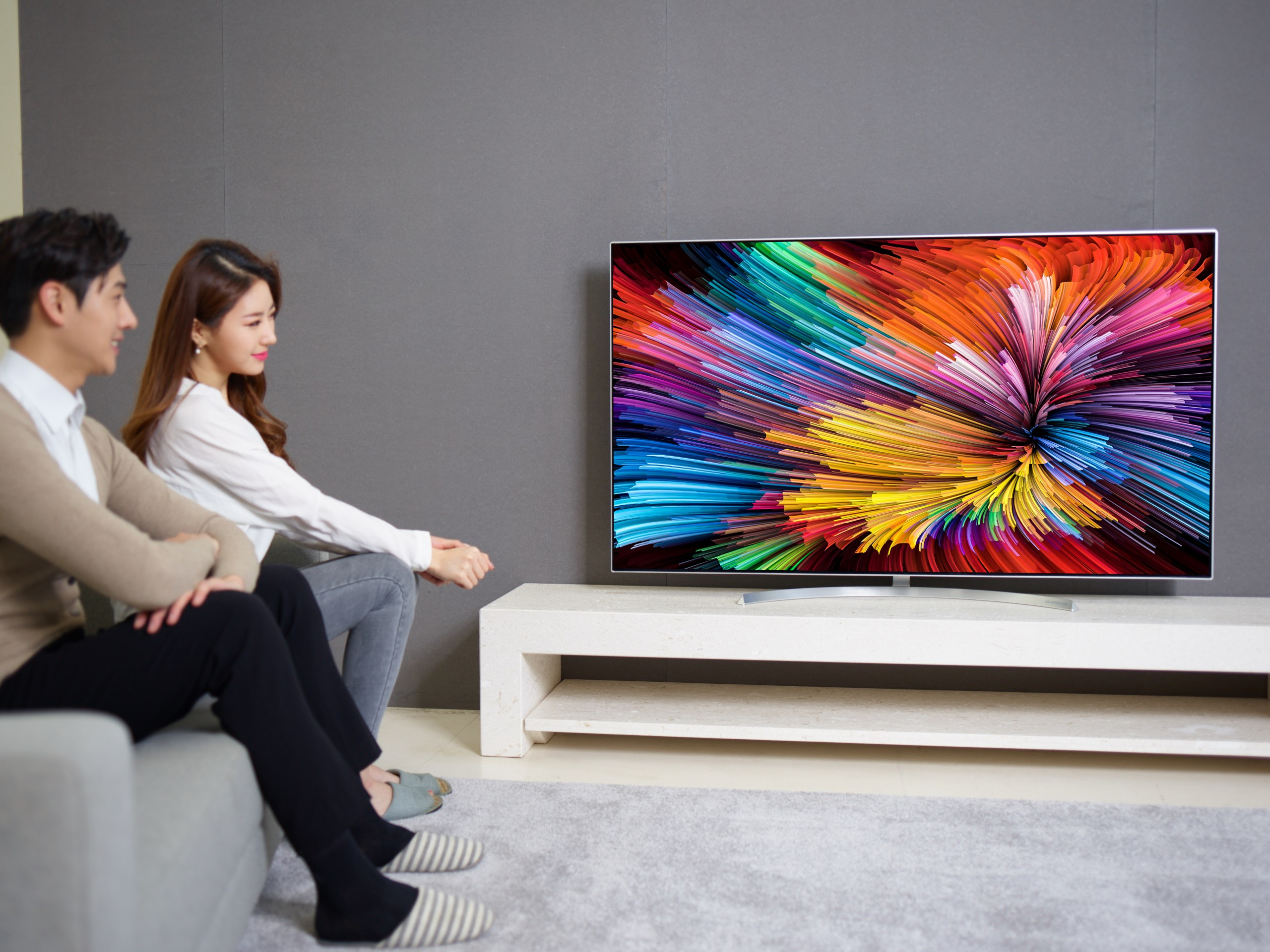 The other view of a couple sitting on a couch watching the LG SUPER UHD TV (model SJ95)