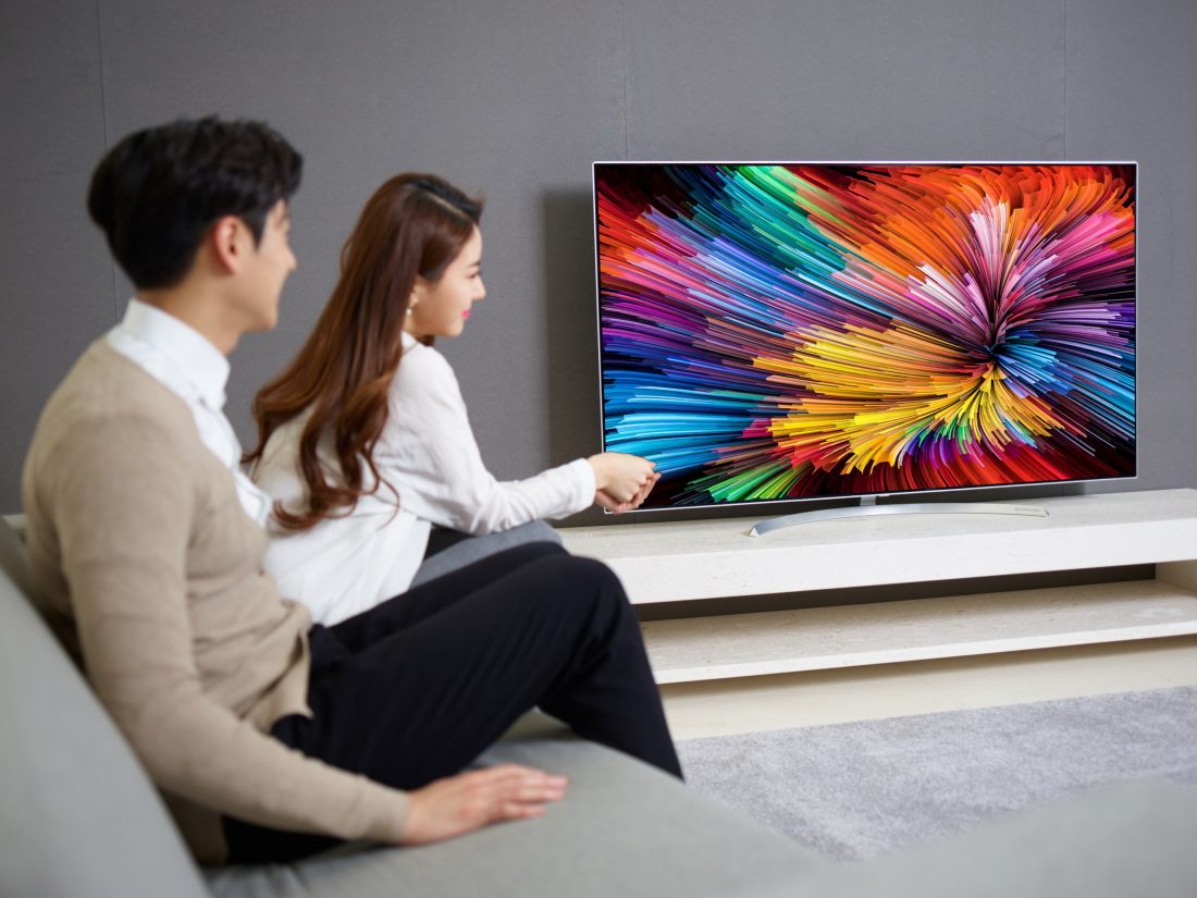 The last image of a couple sitting on a couch watching the LG SUPER UHD TV (model SJ95)