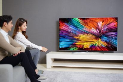 A side view of a couple sitting on a couch while watching colorful imagery on the LG SUPER UHD TV