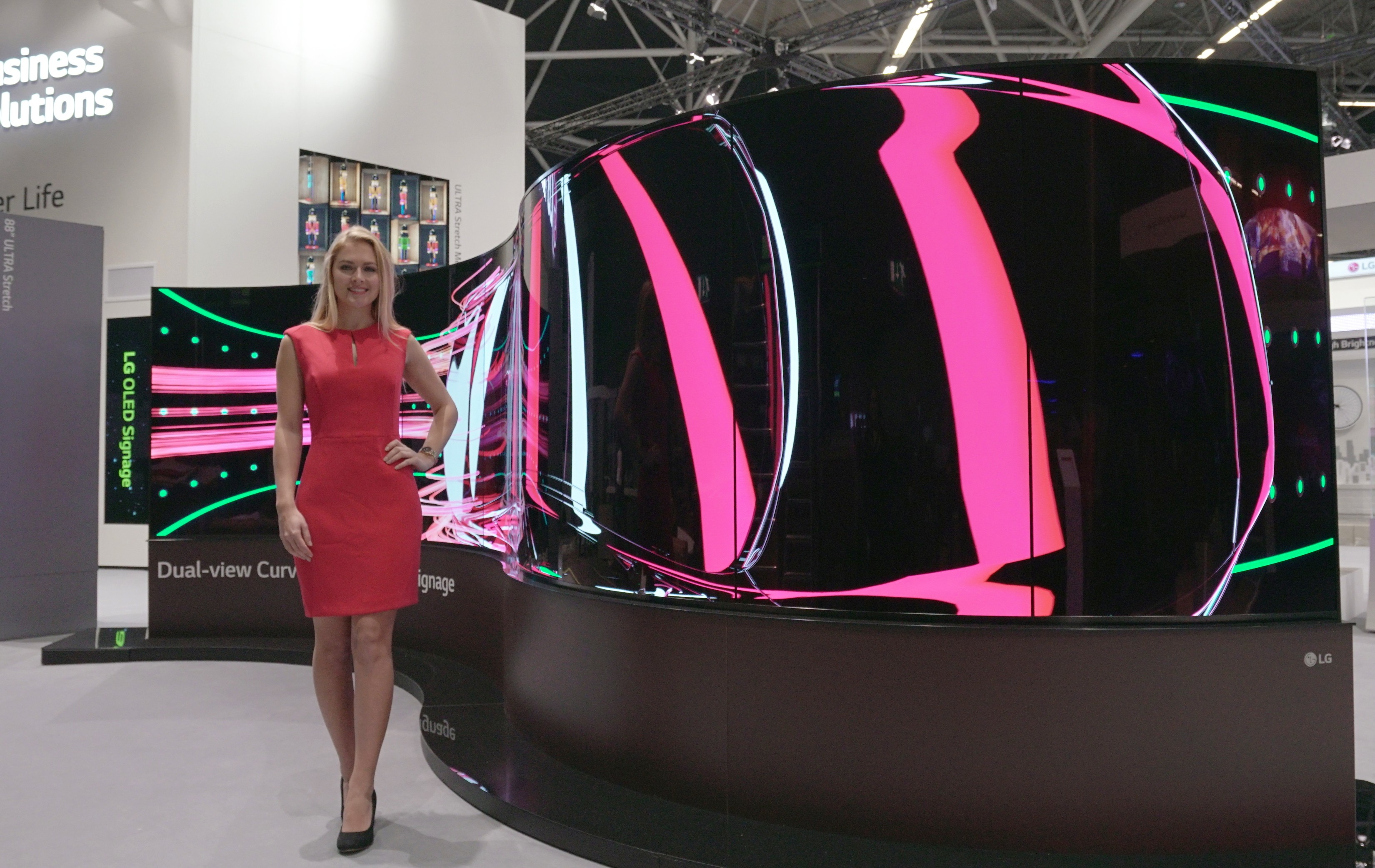 A model standing on the left side of LG's 65-inch Dual-View Curved Tiling OLED signage