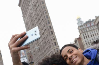 A man and woman take a selfie with the LG G6 in Ice Platinum in front of the Flatiron Building in New York, USA