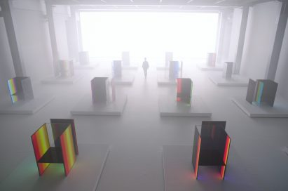 A woman walk around Tokujin Yoshioka's art exhibition hall which is blurred by the fog effect.