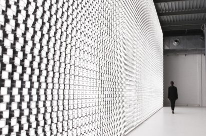 A woman is seen in the background walking beside the back wall of Tokujin Yoshioka's art exhibition, which boasts thousands of bright lights.