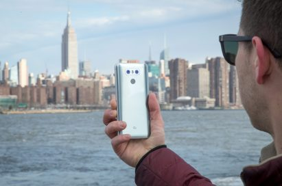 A man holds the LG G6 in Ice Platinum against the New York skyline, showing off the back side of the device