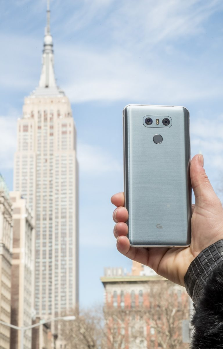 A person holds the LG G6 in Ice Platinum in front of the Empire State Building in New York, USA, showing off the back side of the device