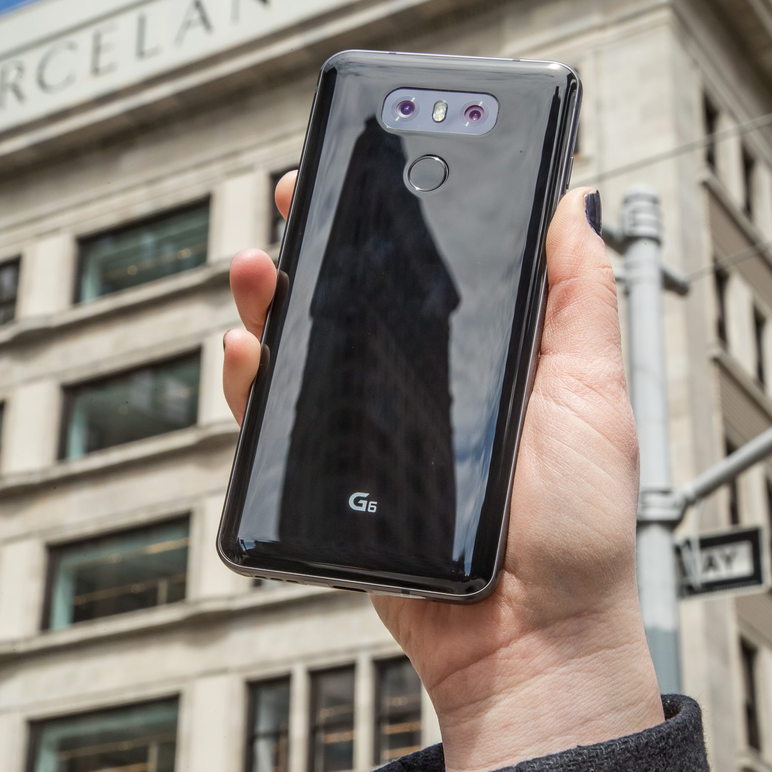 A person holds the LG G6 in Astro Black up in front of a New York building, showing off the back side of the device