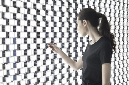 A woman takes a closer look at the back wall of Tokujin Yoshioka's art exhibition, which boasts thousands of bright lights.