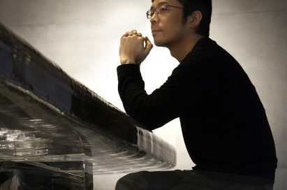 Side profile of Tokujin Yoshioka seated on a table