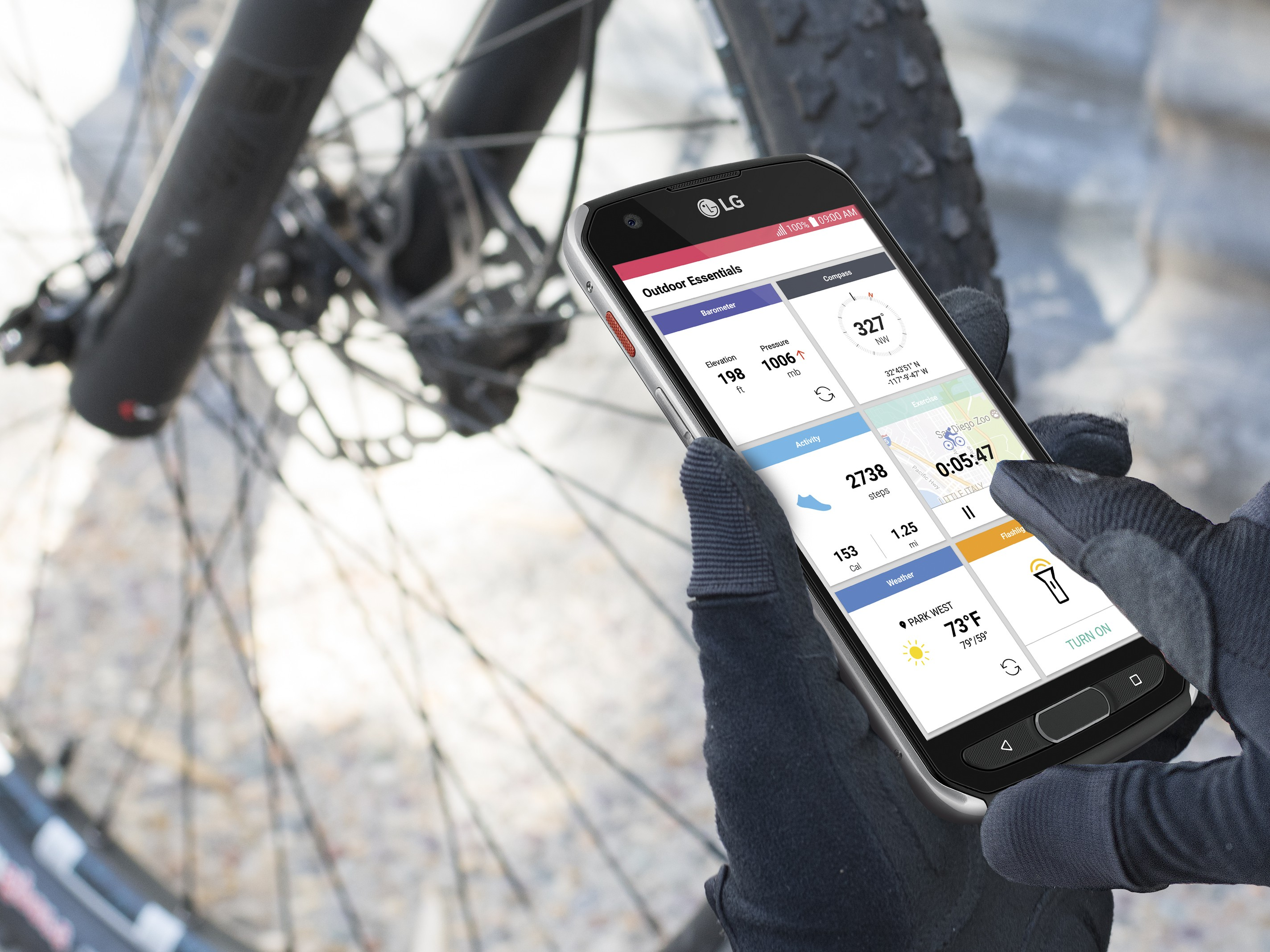 A person in front a bike holding the LG X venture, looking at exercise records on the device's Outdoor Essentials app