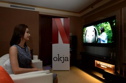 A female model watches Okja on LG's 2017 SIGNATURE OLED TV W alongside a promotional standing banner for the Netflix series