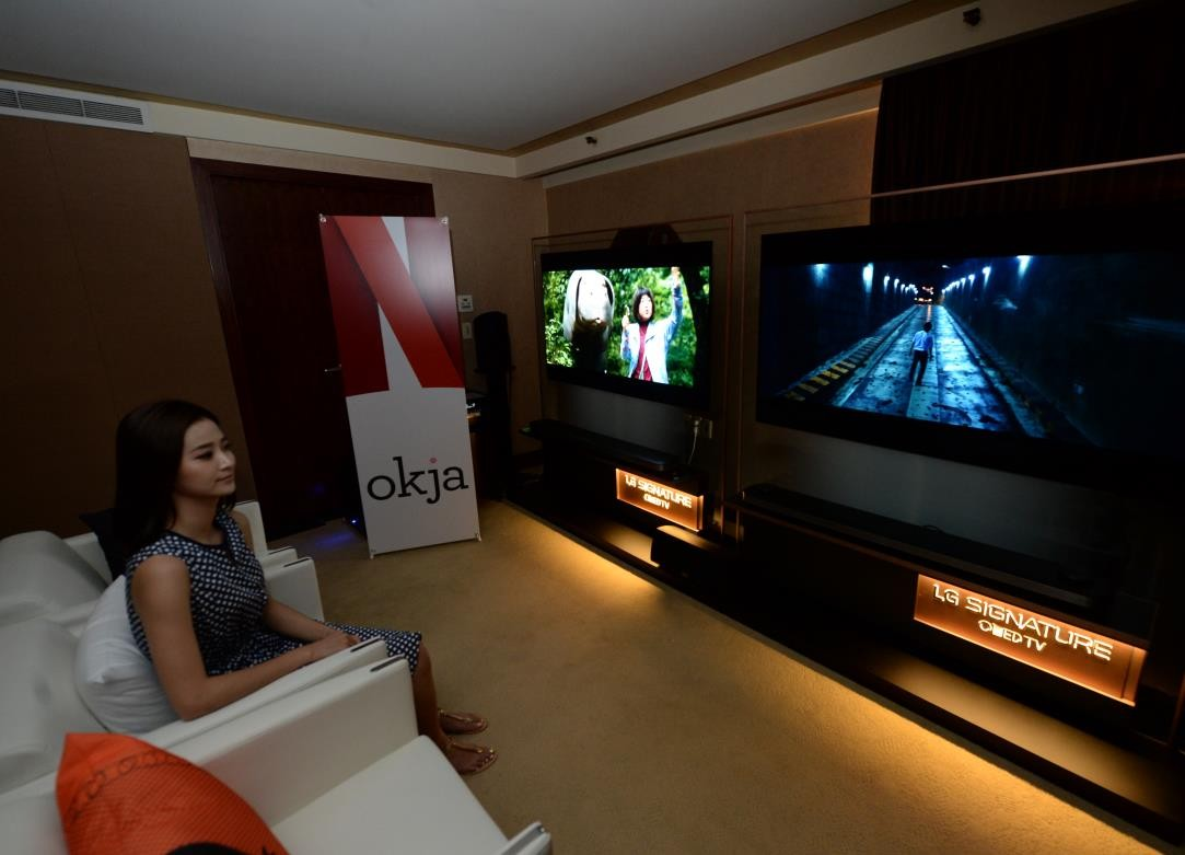 A female model watches Okja on LG's 2017 SIGNATURE OLED TV W, Netflix promotional standing banner visible at side of room