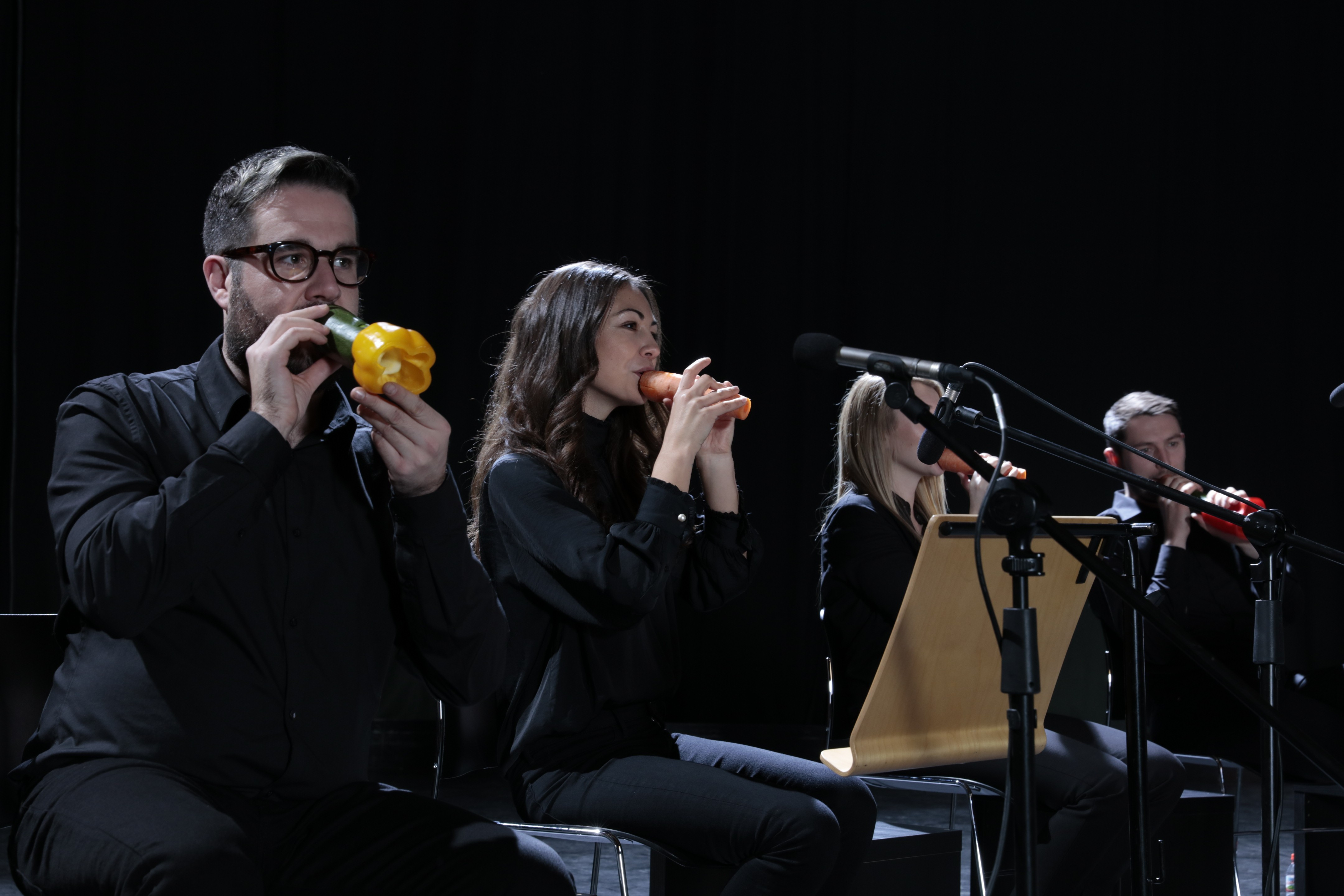 A close-up of four members of the London Vegetable Orchestra performing with their makeshift vegetable instruments.
